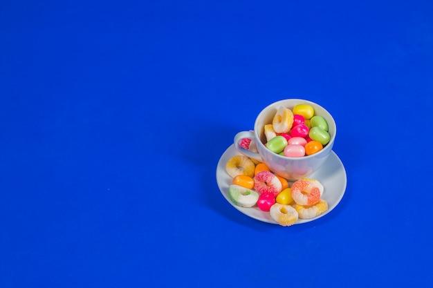 Weiße tasse mit süßer süßigkeit lokalisiert auf blauem hintergrund. schließen sie die auswahl der verschiedenen bunten süßigkeiten in der bäckerei, .candy store ab. party-snack-food-konzept. speicherplatz kopieren
