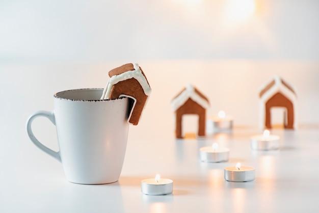 Weiße tasse mit tee, kleinem lebkuchenhaus und kerzen. weihnachts gemütliche feiertage.