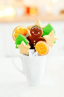 Weiße tasse mit weihnachtsgeschenk, bonbonsternen und weihnachtsbäumen, lebkuchenmann auf heller girlande
