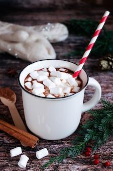 Weiße tasse scharf gewürzter kakao oder schokolade mit marshmallows und einem gestreiften papierstrohhalm auf einer rustikalen hölzernen tischplatte