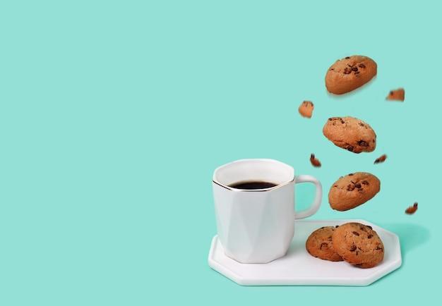 Weiße tasse schwarzen kaffee auf minzhintergrund mit appetitlichen keksen und krümel, die in der luft schweben.