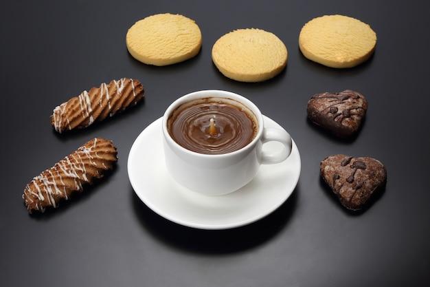 Weiße tasse schwarzen kaffees mit keksen auf einem dunklen