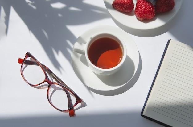 Weiße tasse schwarzen tees mit palmenschatten