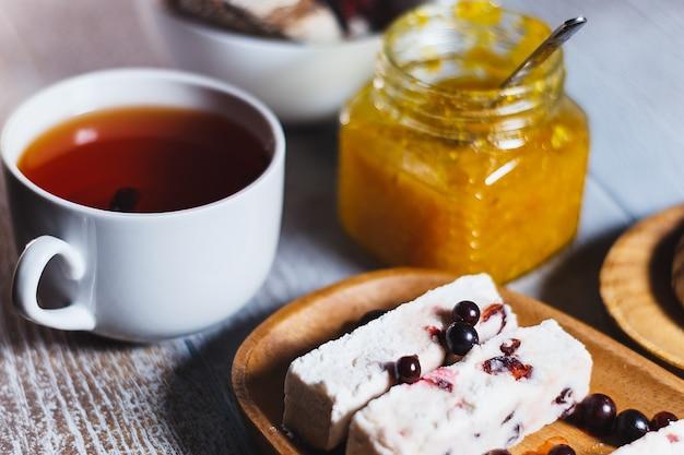 Weiße tasse schwarzer tee mit beeren-marshmallow und glas orangenmarmelade schließen oben. tee-bremssatz.