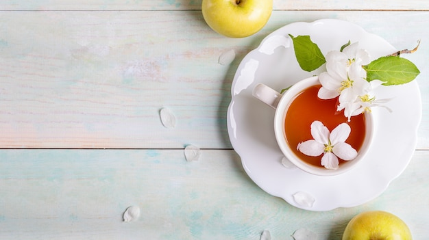 Weiße tasse tee auf geformter untertasse mit blühenden apfelbaumblumen und zwei gelben äpfeln auf holztisch.