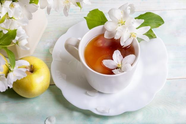 Weiße tasse tee auf geformter untertasse mit blütenapfelbaumblumen und gelbem apfel auf holztisch mit bokeh-nahaufnahme.