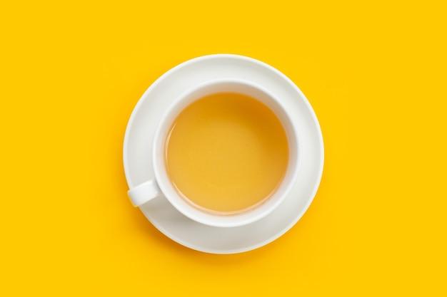 Weiße tasse tee auf gelbem hintergrund