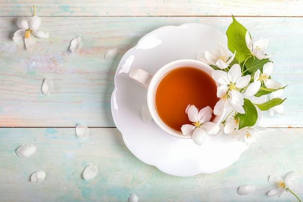 Weiße tasse tee mit blühenden apfelbaumblumen auf geformter untertasse auf gemaltem holztisch.