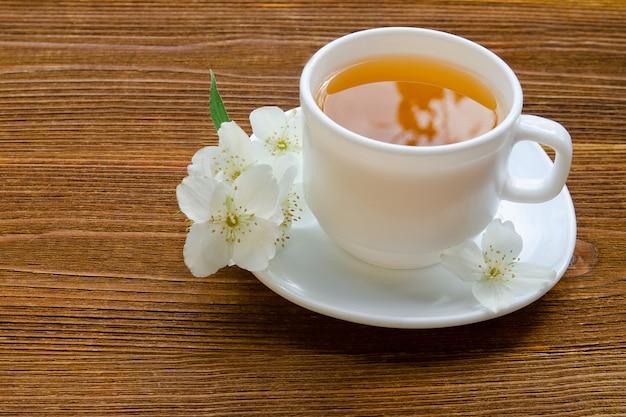 Weiße tasse tee mit jasmin auf holztisch.