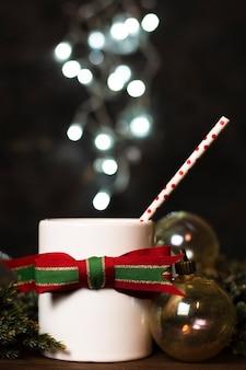 Weiße tasse tee mit weihnachtslichtern im hintergrund
