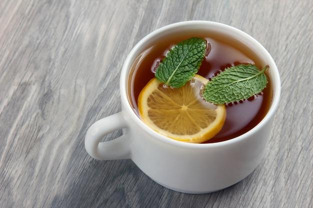 Weiße tasse tee mit zitrone und minze