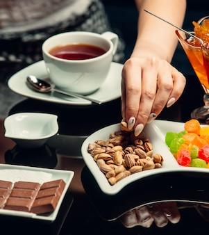 Weiße tasse tee serviert mit schokolade, pistazien