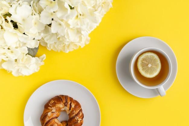 Weiße tasse tee und blumen auf gelbem hintergrund. flat lay draufsicht frühstückskonzept