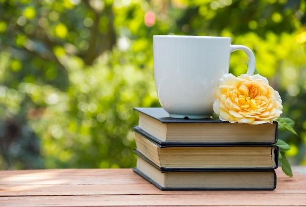 Weiße tasse tee und duftende gelbe rose auf einem holztisch