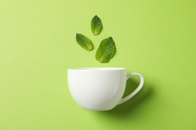 Weiße tasse und blätter auf grün, platz für text
