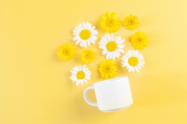 Weiße tasse und kamillenblüten auf gelbem grund. blumen gießen aus einer tasse. surreale komposition mit kamillentee. flach darauf legen.