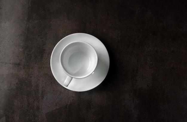 Weiße tasse und untertasse für heißgetränke auf neutralem hintergrund