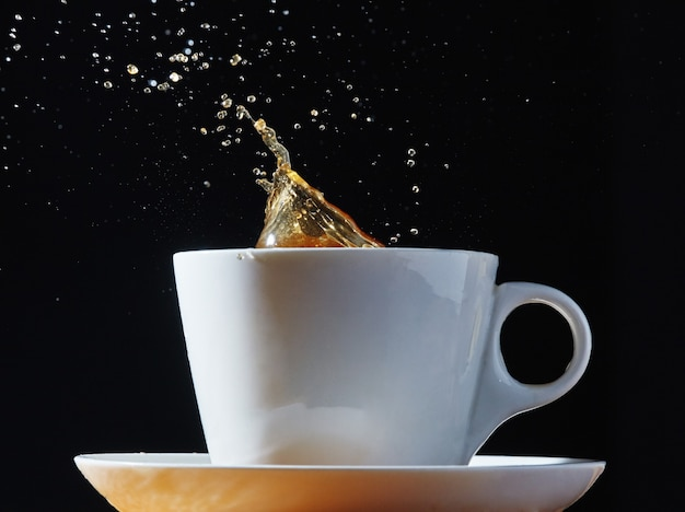 Weiße tasse und untertasse mit einem schuss kaffee.