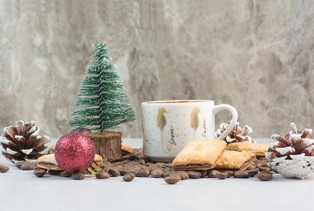 Weiße tasse voll kaffee mit kaffeebohnen und tannenzapfen. hochwertiges foto