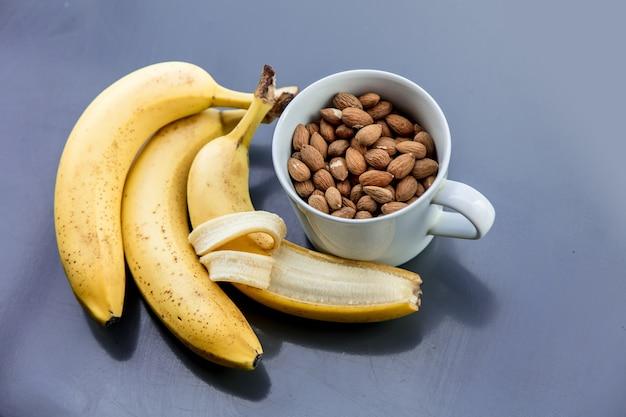 Weiße tasse voll von mandeln mit banane auf grauem hintergrund. ansicht von oben