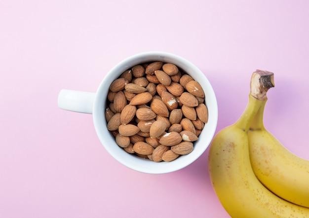 Weiße tasse voll von mandeln mit banane auf rosa hintergrund. ansicht von oben