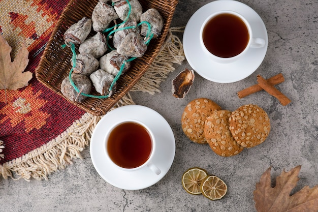 Weiße tassen heißen tee mit getrockneten früchten und haferkeksen auf einem steintisch.