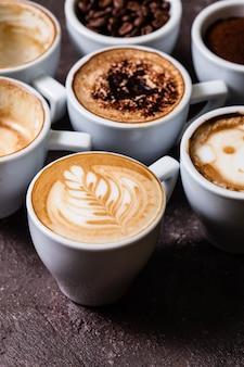 Weiße tassen in verschiedenen phasen der zubereitung von cappuccino. kaffeeliebhaber konzept stillleben