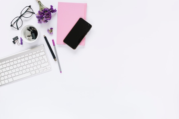 Weiße tastatur und mobiltelefon mit briefpapier auf weißem hintergrund