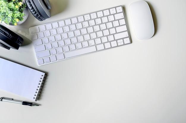 Weiße tastatur und versorgungen des modells auf weißer tabelle, kopienraum für text oder produktanzeige.