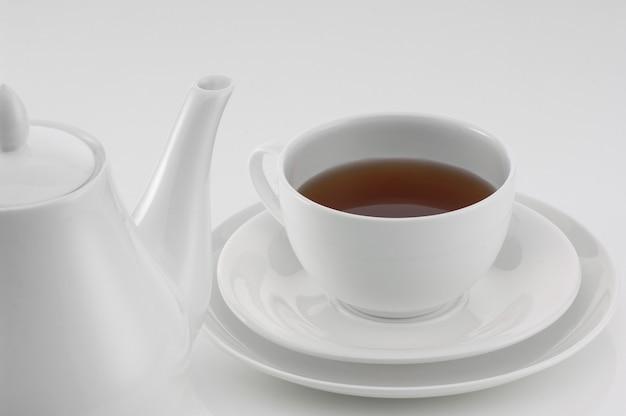 Weiße teekanne aus keramik mit tasse auf hellem hintergrund, nahaufnahme