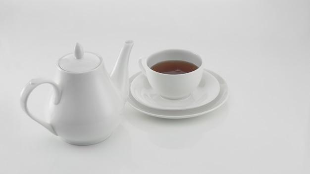Weiße teekanne aus keramik mit tasse auf hellem hintergrund
