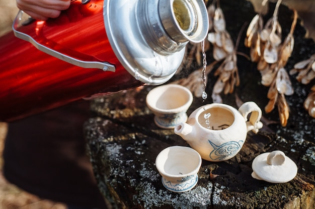 Weiße teekanne aus ton mit blauem muster und zwei trinkschalen