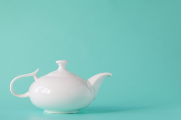 Weiße teekanne isoliert auf aquamarin