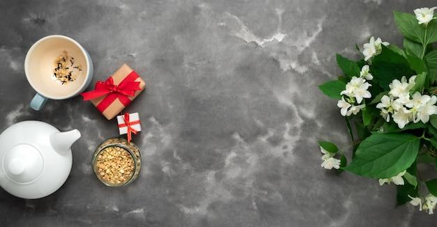 Weiße teekanne kräuter trockener tee jasminblüte tasse geschenk geschenkbox schwarzer weißer marmor hintergrund flach legen tee zeit banner