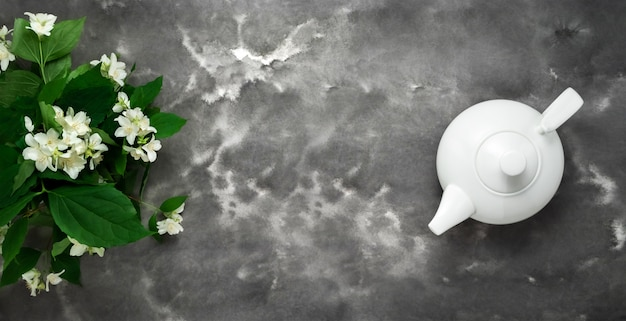 Weiße teekanne, kräutertee, jasminblüte, schwarzer weißer marmorhintergrund flach liegen. tee-draufsichtschablone langes web-banner