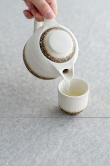 Weiße teekanne mit glas und wasser