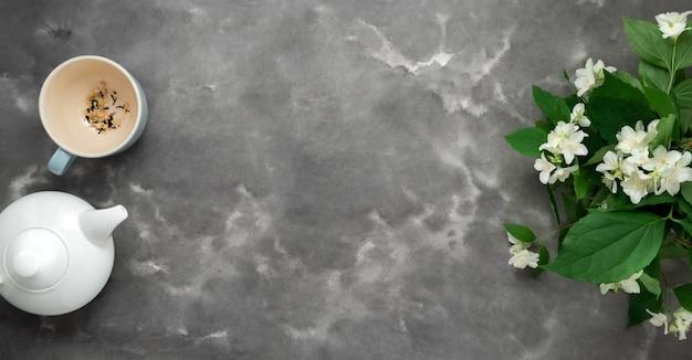 Weiße teekanne, trockener kräutertee, jasminblüte, tasse, schwarzer weißer marmorhintergrund flach liegen. teezeit langes web-banner