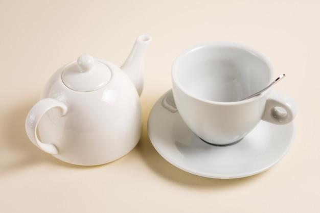 Weiße teekanne und eine leere tasse teelöffel.