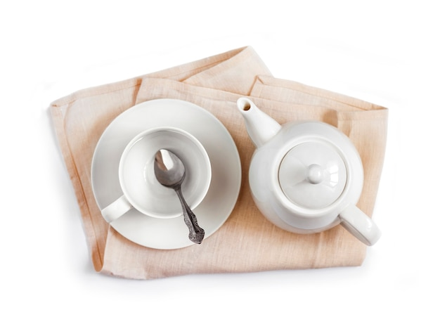 Weiße teekanne und leere teetasse mit löffel auf beigefarbenem tuch isoliert auf weißem hintergrund. flache lage, ansicht von oben