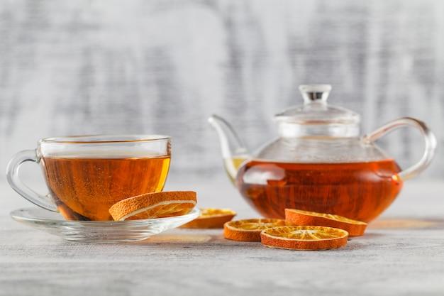 Weiße teetasse mit gewürzen und weihnachtsbaum aus getrockneten orangenscheiben