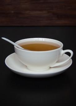 Weiße teetasse mit untertasse und löffel auf dunklem hintergrund