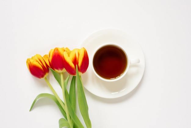Weiße teetasse mit untertasse und roten und gelben tulpen auf weißem hintergrund konzept der liebe und des frühlings. flach liegen