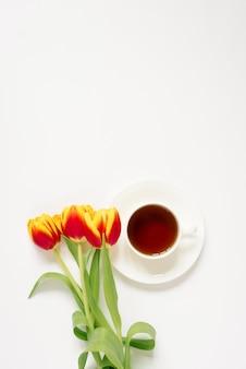 Weiße teetasse mit untertasse und roten und gelben tulpen auf weißem hintergrund konzept der liebe und des frühlings. flacher platz zum legen und kopieren