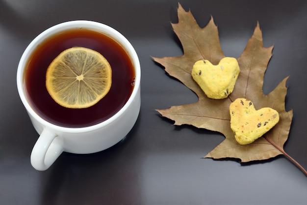 Weiße teetasse mit zitrone auf einer untertasse mit keksen und herbstlaub