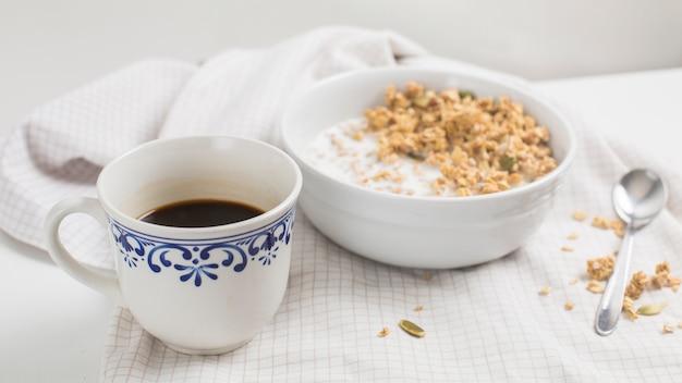 Weiße teetasse; schüssel haferbrei auf tischdecke