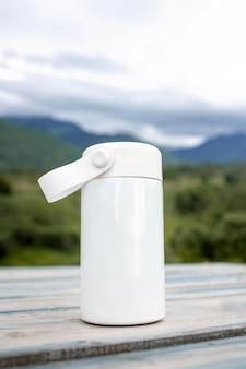 Weiße thermoskanne auf einem hintergrund der berge.