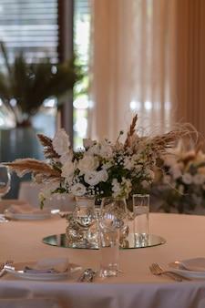 Weiße tischdecken mit klaren vasen und weißen chrysanthemen- und farnarrangements