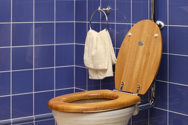 Weiße toilette auf blauer fliesenwand