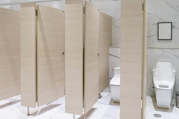 Weiße toiletten der nahaufnahme im badezimmer, design von weißen keramischen pissoirs im toilettenraum