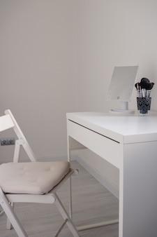 Weiße toilettentischkommode mit einem spiegel und make-up-pinseln auf einer weißen oberfläche in einem modernen innenraum